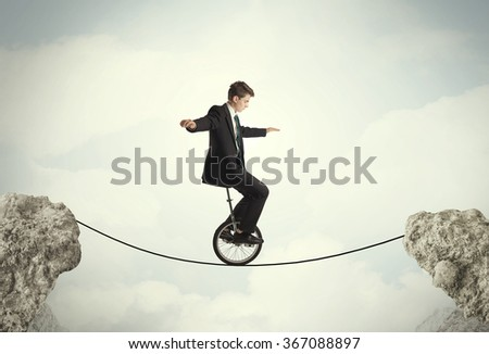 Brave business man riding an mono cycle between cliffs concept - stock photo