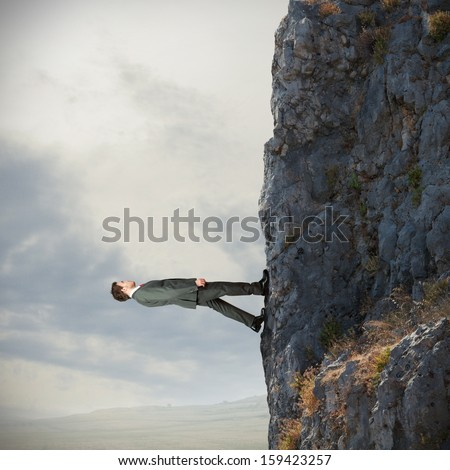 Brave businessman walks vertically over the mountain - stock photo