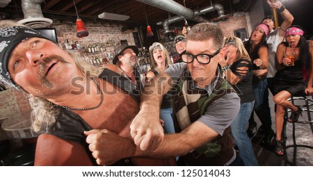 Brave geek with glasses punches biker gang man in bar - stock photo