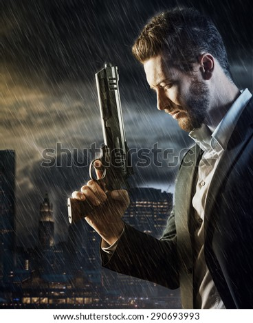 Brave handsome male agent under pouring rain holding a gun, city skyline and cloudy sky at sunset on background, crime and danger concept - stock photo