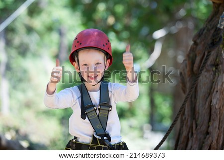 brave little boy having fun at adventure park and giving double thumbs-up - stock photo