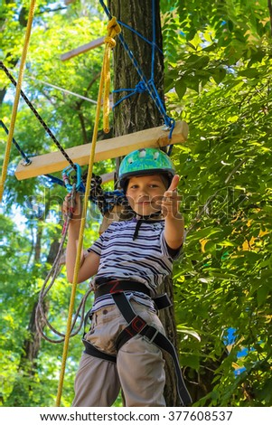 Brave little boy having fun at adventure park and giving  thumbs-up - stock photo