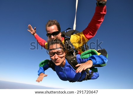 brave man and fearless woman , jumping from plane practicing skydiving in Brazil - stock photo