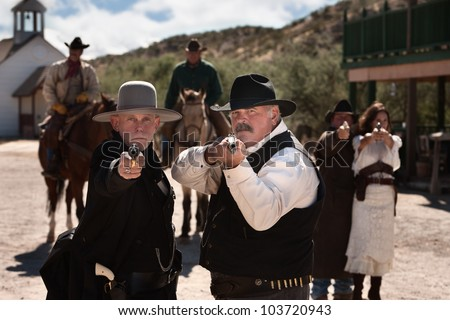 Brave men aim their guns in old west town - stock photo