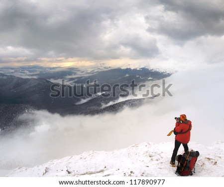 brave photographer takes pictures in the snowy mountains - stock photo
