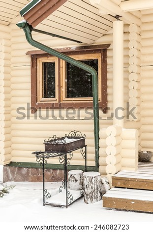 Brazier near the wooden snow-covered house and birch logs - stock photo