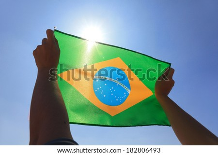 Brazil flag in hand with sky and sun - stock photo