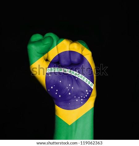 Brazil flag on fist over black background. Symbol of strength. - stock photo
