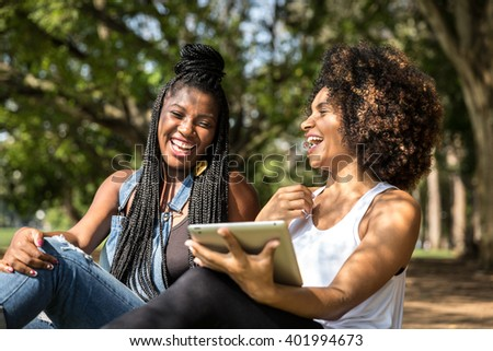 Brazilian afro women using tablet computer in the park - stock photo