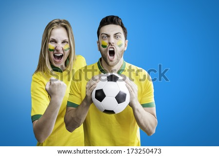 Brazilian couple celebrate on blue background with her face painted - stock photo