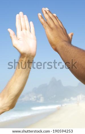 Brazilian diversity interracial hands high five Ipanema Beach Rio de Janeiro Brazil - stock photo