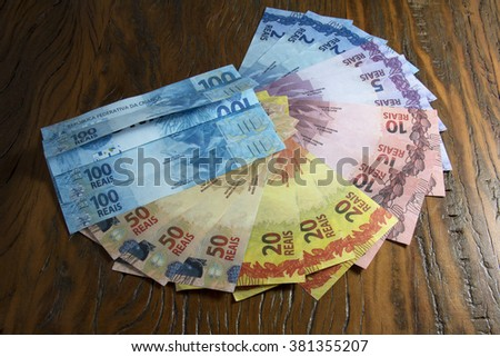 Brazilian fake money, bills and coins in a shape of a pizza in a wooden background - stock photo