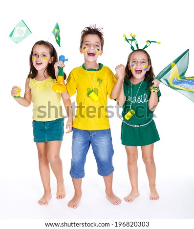 brazilian fans kids supporting brazil and wearing green and yellow clothes, with vuvuzelas and flags. - stock photo