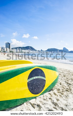 Brazilian flag stand up paddle surfboards stacked on the beach at Copacabana, Rio de Janeiro Brazil - stock photo