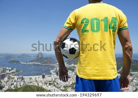 Brazilian football player in 2014 shirt standing with football bright sunny Rio de Janeiro skyline with Sugarloaf Pao de Acucar Mountain - stock photo