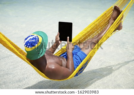 Brazilian man uses tablet computer relaxing in hammock on beach over the sea - stock photo