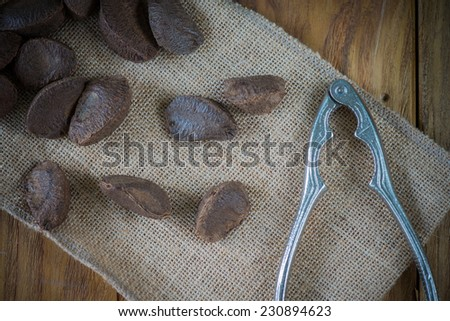 Brazilian nuts and nut crasher on wooden table - stock photo
