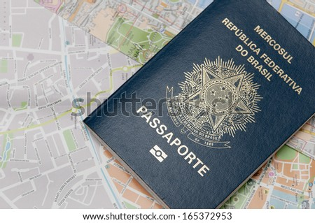 Brazilian passport above a map / A passport is a government-issued document that certifies the identity and nationality of its holder for the purpose of international travel. - stock photo