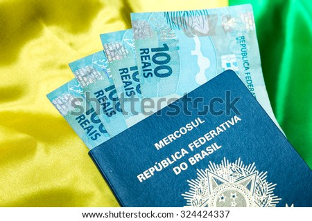 Brazilian passport and brazilian currency (100 Reais) on the table - stock photo
