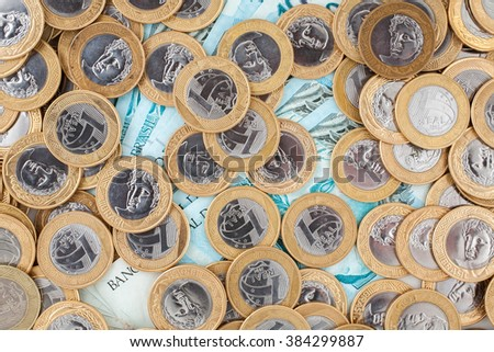 Brazilian 1 Real coins and 100 Reais bank notes - stock photo