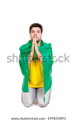 Brazilian soccer fan or supporter worried and praying in the championship or competition or cup. - stock photo