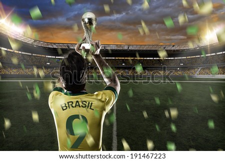 Brazilian soccer player, celebrating the championship with a trophy in his hand. - stock photo