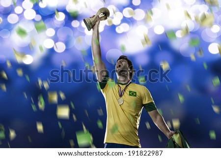 Brazilian soccer player, celebrating the championship with a trophy in his hand, on a blue background. - stock photo