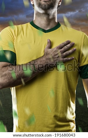 Brazilian soccer player, listening to the national anthem with his hand on his chest. - stock photo