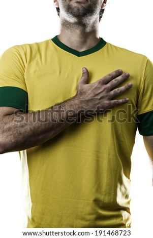 Brazilian soccer player, listening to the national anthem with his hand on his chest, on a white background. - stock photo