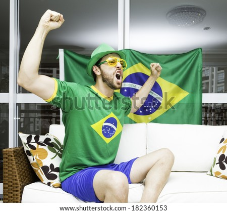 Brazilian supporter celebrates at home - stock photo