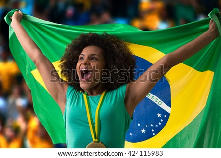 Brazilian woman fan holding the Brazilian flag in the stadium - stock photo