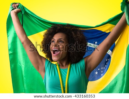 Brazilian woman fan on yellow background - stock photo