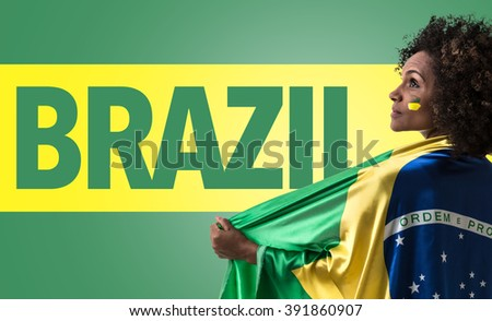 Brazilian woman holding the flag of Brazil and the Text: Brazil - stock photo