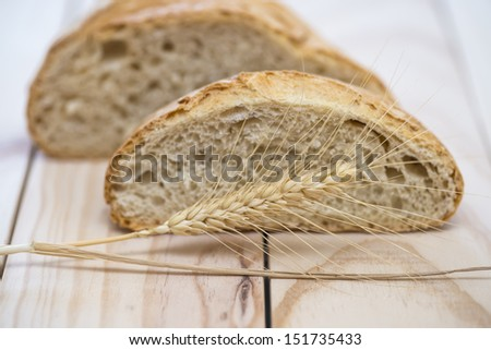 Bread and a wheat ear on a wooden background. - stock photo