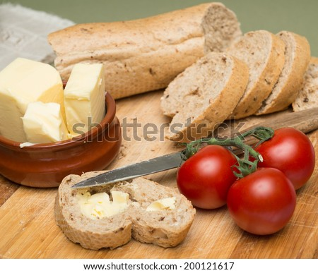 Bread and butter/Delicious organic home-made bread and butter with ripe tomatoes on wooden board - stock photo