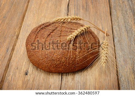 bread and ears of wheat on the wooden table - stock photo