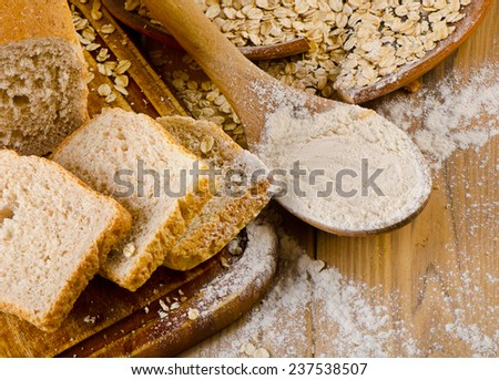 Bread and flour on a  wooden background. Selective focus - stock photo
