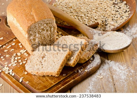Bread and flour on  wooden background. Selective focus - stock photo