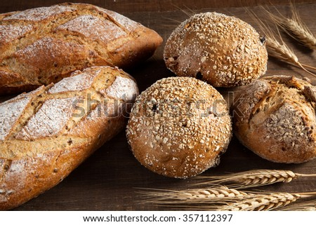 Bread and wheat ears on wooden background - stock photo