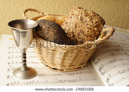 Bread and wine on a sheet music - stock photo