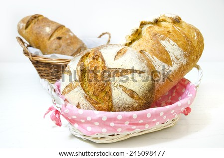 Bread. Composition with bread in wicker basket isolated on white - stock photo
