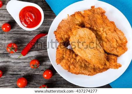 bread crumb coated fried chicken breast on a white dish on a table mat with red chili pepper, tomatoes and ketchup on an old rustic wooden background, top view  - stock photo