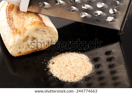 bread crumbs grated on kitchen table  - stock photo