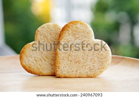 Bread cut in the shape of hearts, with nature background. Concept about love and relationship.                          - stock photo