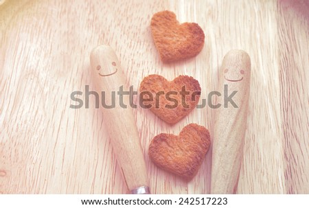 Bread cutting in shape of heart and wooden spoons. (Concept about love and happiness) - stock photo