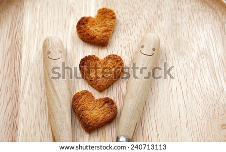 Bread cutting in shape of heart and wooden spoons with smiley. (Concept about love and happiness) - stock photo