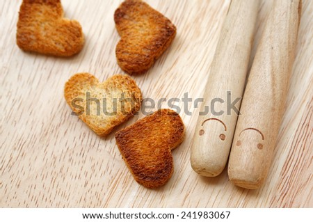 Bread cutting in shape of heart and wooden spoons with smiley. Concept about love and happiness.                        - stock photo