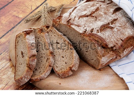 bread on cutting board on wooden background  - stock photo