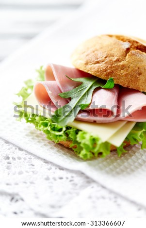Bread roll with ham and lettuce  - stock photo