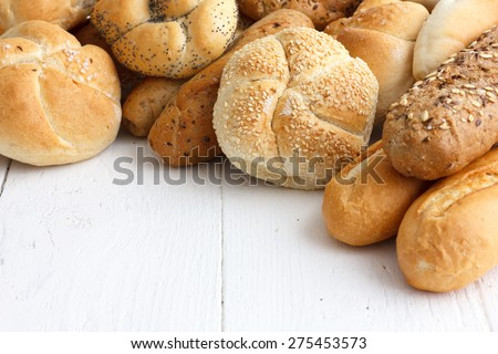 Bread rolls and baguettes on rustic white painted wood. - stock photo